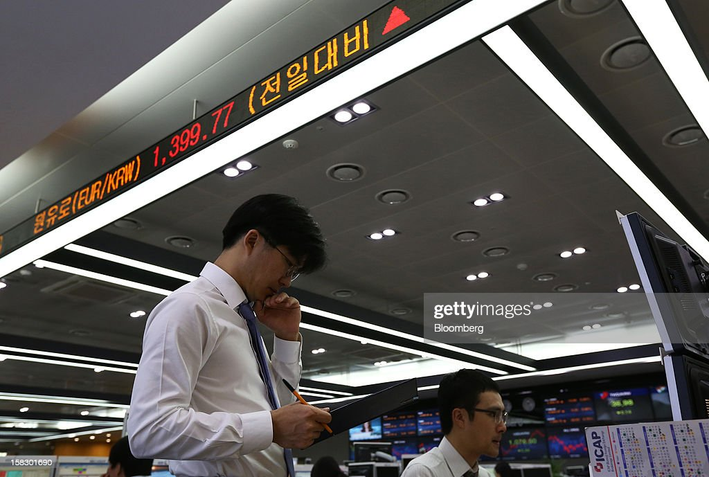 Foreign currency dealers work in a dealing room at the Korea Exchange Bank headquarters in Seoul, South Korea, on Wednesday, Dec. 12, 2012. South Korea's won traded near a 15-month high and stocks extended gains after North Korea launched a rocket in defiance of international sanctions. Photographer: SeongJoon Cho/Bloomberg via Getty Images