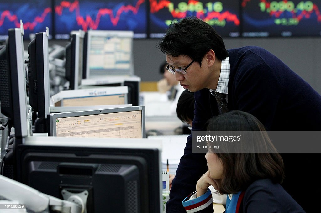 Foreign currency dealers work in a dealing room at the Korea Exchange Bank headquarters in Seoul, South Korea, on Tuesday, Feb. 12, 2013. North Korea conducted its third underground nuclear test today, underscoring a disregard for an international community that has already isolated the totalitarian state from the global economy. Photographer: SeongJoon Cho/Bloomberg via Getty Images