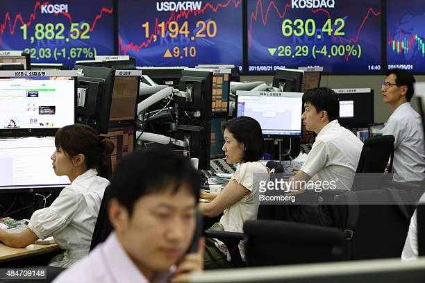 Foreign currency dealers work in front of monitors displaying the Korea Composite Stock Price Index left and the exchange rate between the South...