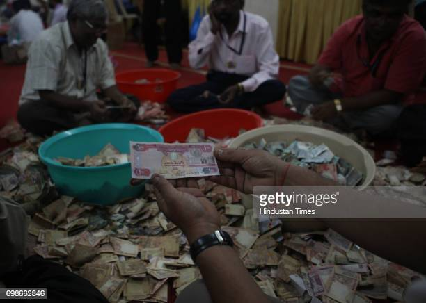 A foreign currency note being donated by a devotee Volunteers of Lalbaugcha Raja open the donation box kept at Ganpati pandal Rupees 1 Crore 1 Lakh...