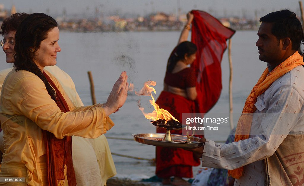A foreign devotee move her hands towards the flames presented by a priest at Sangam, in Kumbh Mela area, on February 13, 2013 in Allahabad, India. The mega religious fair is held once in 12 years in Allahabad and the fourth official bathing is set to take place on 'Basant Panchami' on February 15, 2013.