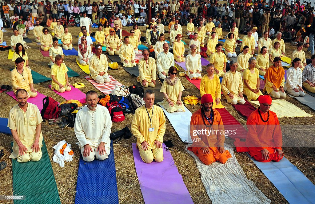 Foreign devotees participate in a session of yoga on the banks of the Sangam during the Kumbh Mela Festival in Allahabad on January 16, 2013. The Kumbh Mela in the Indian town of Allahabad will see up to 100 million worshippers gather over the next 55 days to take a ritual bath in the holy waters, believed to cleanse sins and bestow blessings. AFP PHOTO/ Sanjay KANOJIA