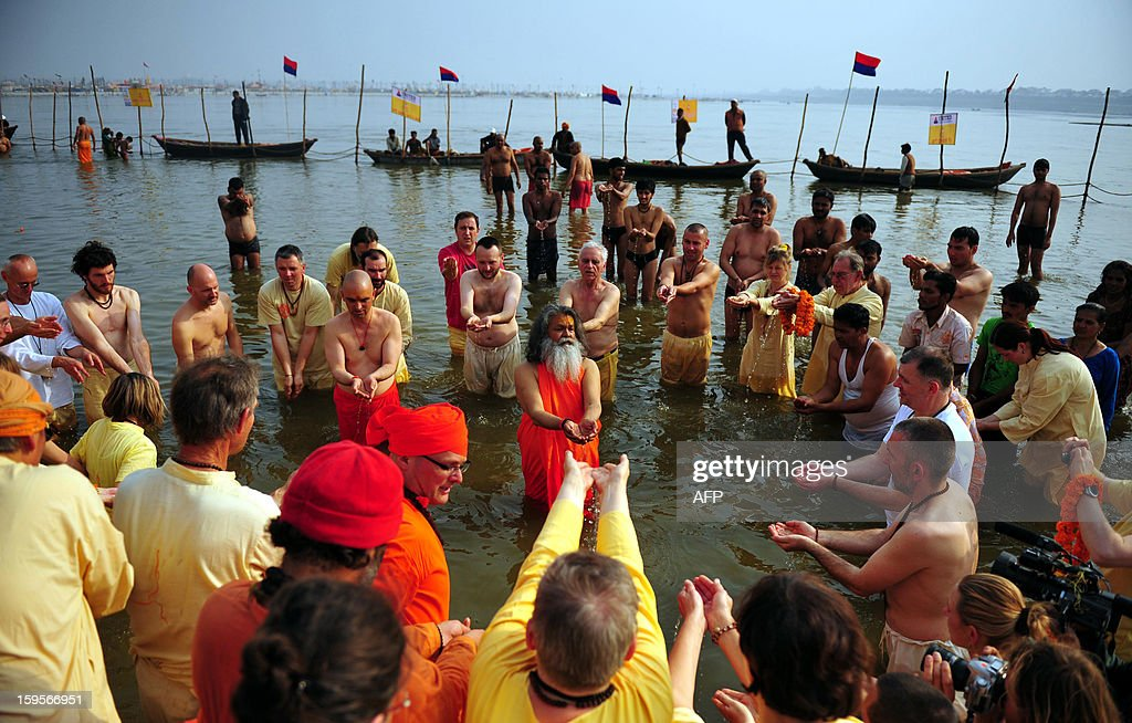 Foreign devotees perform prayers after a session of yoga on the bank of the Sangam during the Kumbh Mela Festival in Allahabad on January 16, 2013. The Kumbh Mela in the Indian town of Allahabad will see up to 100 million worshippers gather over the next 55 days to take a ritual bath in the holy waters, believed to cleanse sins and bestow blessings. AFP PHOTO/ Sanjay KANOJIA