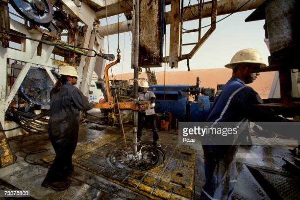 Foreign 'guest workers' drill at the Saudi Aramco oil field complex facilities at Shaybah in the Rub' al Khali desert on March 2003 in Shaybah Saudi...