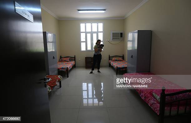 A foreign journalist films a bedroom of the labour city in Doha on May 3 which was built by the Qatari government and will be hosting some 75000...