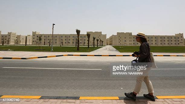 A foreign journalist takes pictures of the labour city in Doha on May 3 which was built by the Qatari government and will be hosting some 75000...