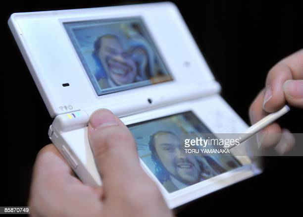 Foreign journalists play with Nintendo's portable video game console DSi before a press conference by Nintendo president Satoru Iwata and games...