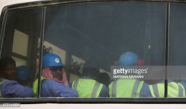 Foreign laborers working on the construction site of the alWakrah football stadium one of the Qatar's 2022 World Cup stadiums sit in a bus as they...