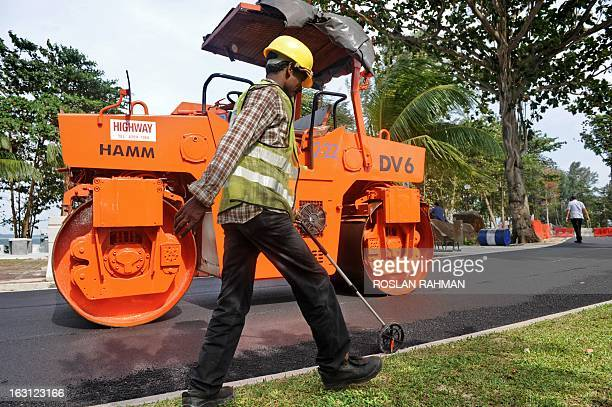 A foreign labourer measures the length of the track surface for jogging and cycling users along the Changi beach in Singapore on March 5 2013 Growth...