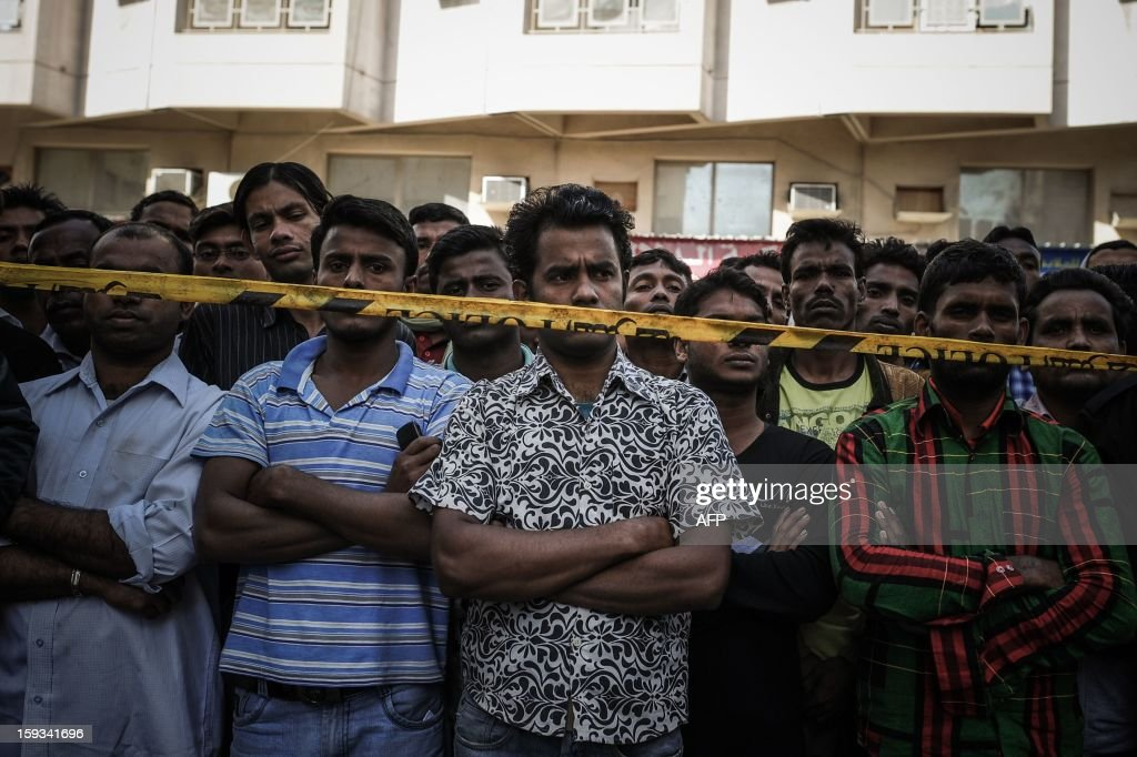Foreign labourers residing in Bahrain stand behind a police cordon as firemen and rescue workers inspect a building where a fire broke out in Manama on January 12, 2013. A fire in a three-storey block housing Asian workers in the Bahraini capital killed at least 13 people, the state BNA news agency reported. AFP PHOTO/MOHAMMED AL-SHAIKH