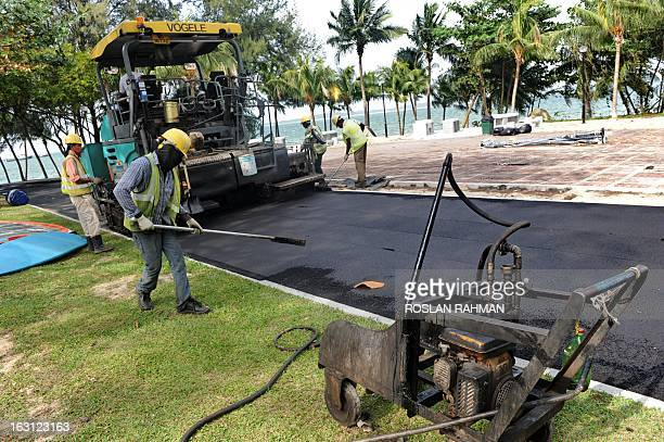 Foreign labourers work on the surfacing of jogging and cycling tracks along the Changi beach in Singapore on March 5 2013 Growth in Singapore's...