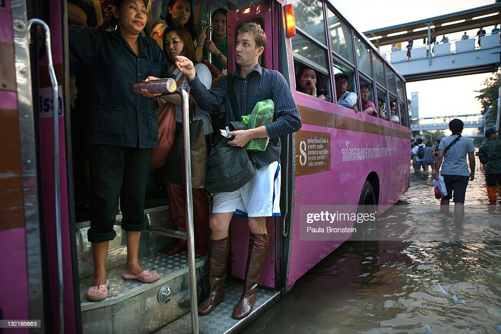A foreign man pays his bus fare as commuters head home by the city bus through heavily flooded downtown streets November 10, 2011 in Bangkok, Thailand. Over seven major industrial parks in Bangkok and, thousands of factories have been closed in the central Thai province of Ayutthaya and Nonthaburi with millions of tons of rice damaged. Across the country, the flooding which is now in its third month has affected 25 of Thailand's 64 provinces. Thailand is experiencing the worst flooding in over 50 years which has affected more than nine million people. Over 400 people have died in flood-related incidents since late July according to the Department of Disaster Prevention and Mitigation.