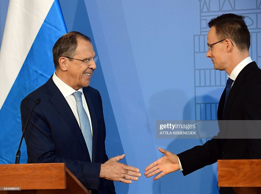 Foreign Minister Sergei Lavrov (L) of Russia shakes hands with Hungarian counterpart Peter Szijjarto (L) at the ministry in Budapest on May 25, 2016 after their joint press conference. / AFP / ATTILA