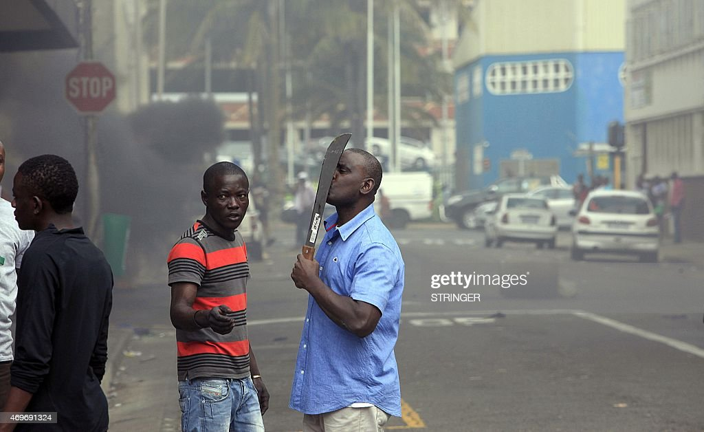 A foreign national holds a machete to protect himself after clashes broke out between a group of locals and police in Durban on April 14 2015 in...