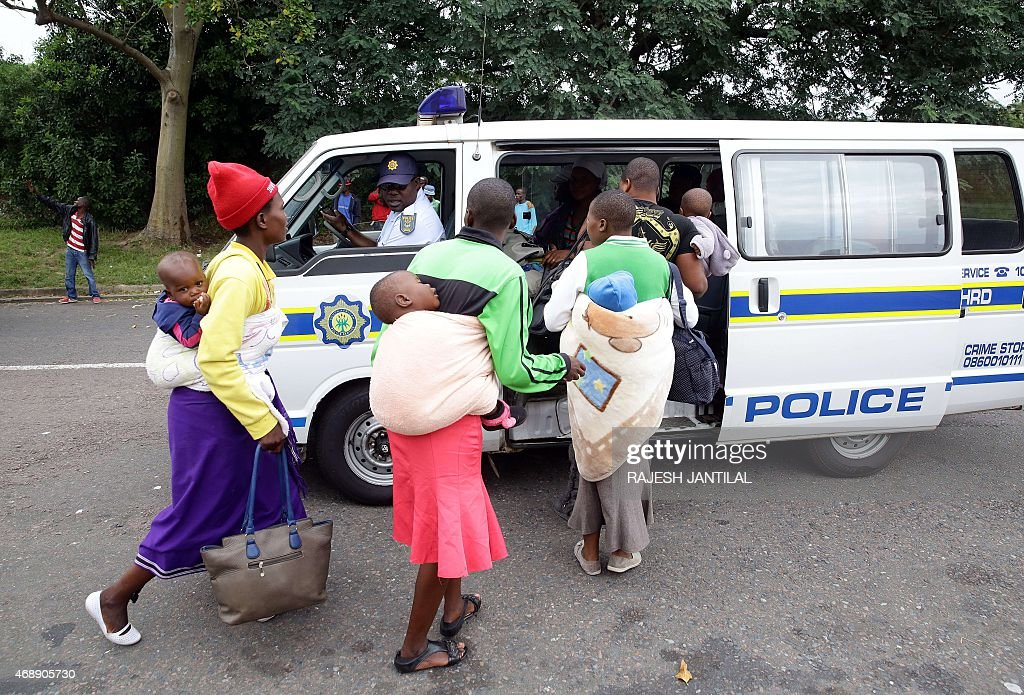Foreign nationals are escorted by members of the South African Police Service after a xenophobic attack in Durban on April 8 2015 Hundreds of people...