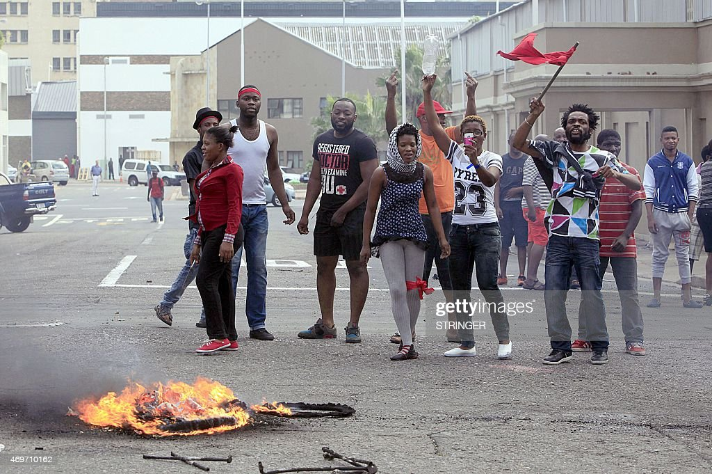 Foreign nationals gesture after clashes broke out between a group of locals and police in Durban on April 14 2015 in ongoing violence against foreign...