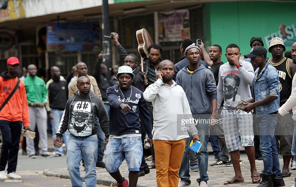 Foreign nationals stand with stones and bricks after a skirmish with locals as thousands of people take part in a 'peace march' against xenophobia in...