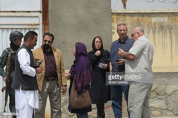 Foreign nationals talk with Afghan security personnel at the gate of the Cure hospital in Kabul on April 24 2014 A guard shot dead three foreigners...