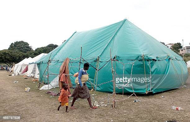 Foreign nationals walk in front of a tent as they have taken shelter to the Chatsworth sports grounds south of Durban on April 15 2015 Hundreds of...