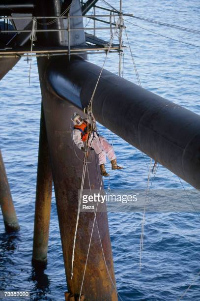 A foreign oil company worker in a fully encapsulated protective biochemical suit rappels down a rope to the lowest pylons to apply an antirust...