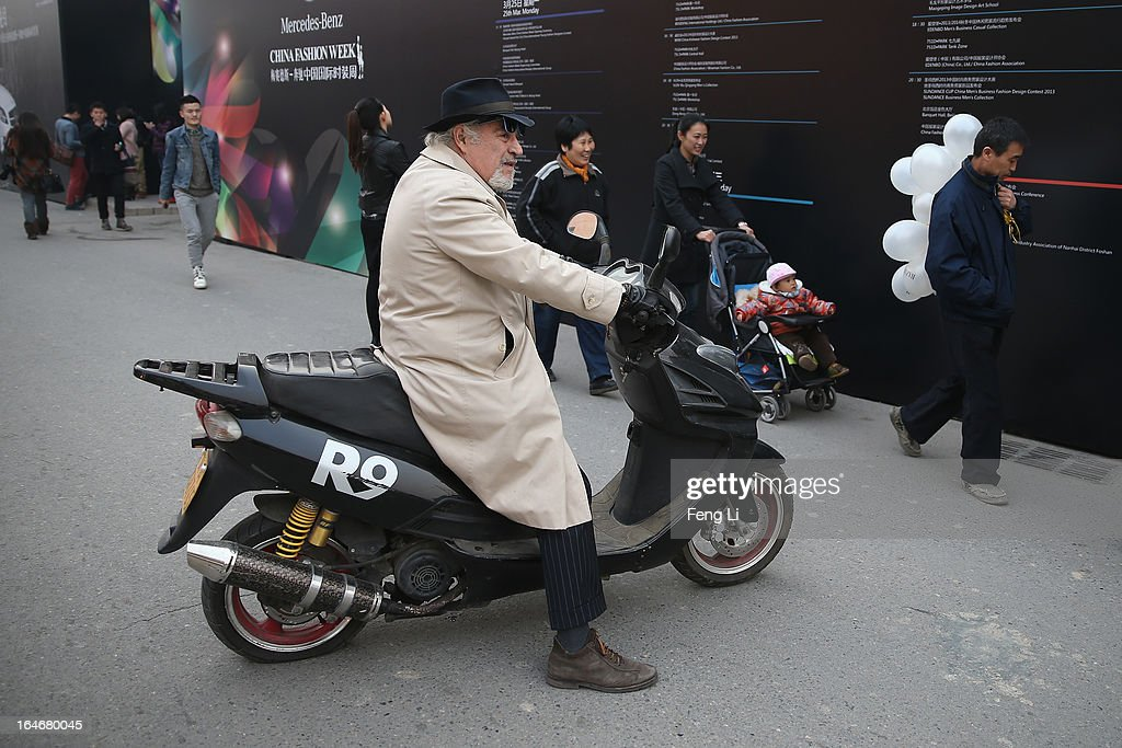 A foreign old man rides the motorcycle as a Chinese old man walks past with balloons on his shoulder on the third day of Mercedes-Benz China Fashion Week Autumn/Winter 2013/2014 at 751 D.PARK Workshop on March 26, 2013 in Beijing, China.