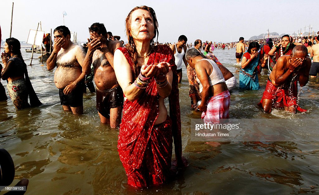A foreign pilgrim takes a holy dip at the Sangam, confluence of rivers Ganga , Yamuna and mythical Saraswati on the occasion of Paush Purnima on January 27, 2013 in Allahabad, India. Millions of Hindu pilgrims are expected to take part in the large religious congregation of a period of over a month on the banks of Sangam during the Maha Kumbh Mela in January 2013, which falls every 12th year.