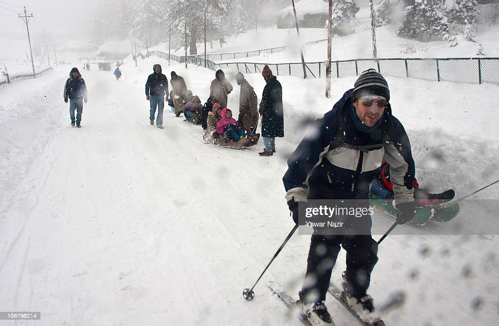 A foreign skier tries to hold onto the rear of a vehicle during a snowfall on December 29, 2012 in Gulmarg, 54 km (35 miles) to the west of Srinagar, the summer capital of Indian-administered Kashmir, India. With the second round of heavy snowfall in Kashmir valley, skiers from around the globe have descended on the ski resort of Gulmarg, known for long-run skiing, snow-boarding, heli-skiing and steep mountains. Gulmarg is located less than six miles from the ceasefire line or Line of Control (LoC) that divides Kashmir between India and Pakistan. As a sense of normalcy has started to return to this strife-torn region, various foreign governments, including the United Kingdom, have lifted the travel advisory to its citizens traveling to Kashmir, raising the hopes of the local tourism industry, officials said.