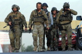 Foreign soldiers leave the Intercontinental Hotel at the end of a military operation against Taliban militants who had stormed the hotel in Kabul on...