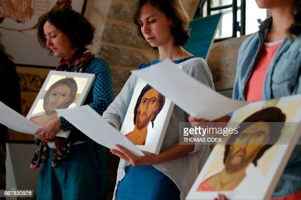 Foreign students of the Bethlehem Icon Center present the works executed during their course to be blessed by an archbishop in the biblical West Bank...