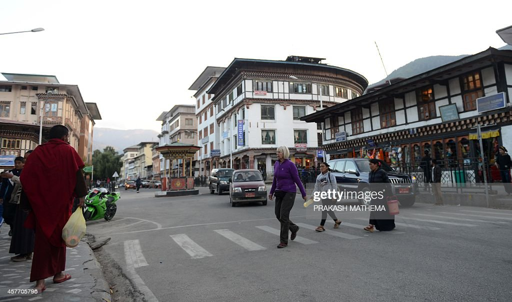 A foreign tourist crosses a street as local pedestrians walk in Thimphu on October 23 2014 Google provided a sneak peek into Bhutan October 23 by...