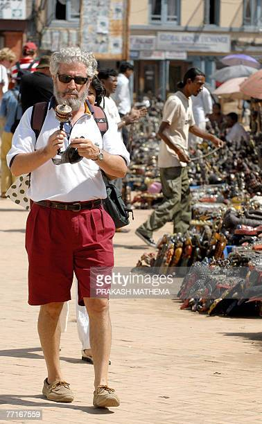 A foreign tourist examines a souvenir purchase as he walks through Durbar Square in Kathmandu 03 October 2007 Tourist arrivals in Nepal have shot up...