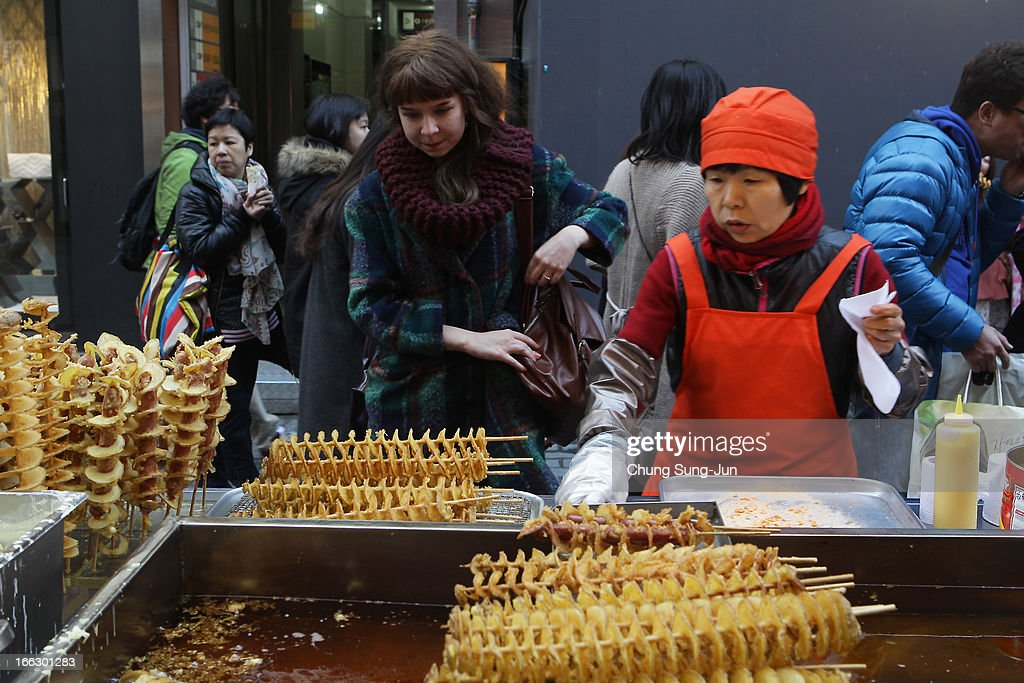 A foreign tourist inspects the wares of a street food vendor in the Myungdong shopping district on April 11, 2013 in Seoul, South Korea. According to reports a North Korean missile launcher has been moved into firing position as the continuing threats of attack emit from Pyongyang. G8 leaders have convened in London to discuss the situation.