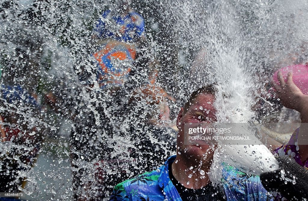 A foreign tourist (C) is splashed with water by an elephant during a water battle in the street as people celebrate ahead of the Songkran Festival for the Thai New Year in Ayutthaya province on April 9, 2014. Songkran is the Thai New Year, which this year starts on April 13, when people celebrate in various ways, including splashing water at each other. AFP PHOTO / PORNCHAI KITTIWONGSAKUL