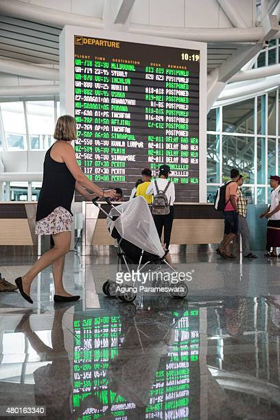 A foreign tourist looks flight schedule information board at Ngurah Rai International airport on July 10 2015 in Denpasar Bali Indonesia 277 flights...