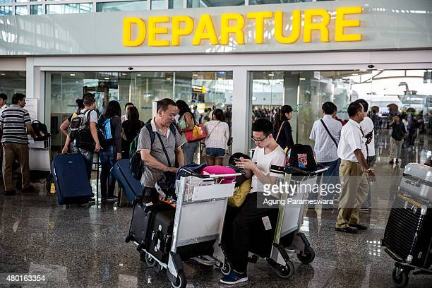 A foreign tourist plays his smartphone as he wait flights schedule information at Ngurah Rai International airport on July 10 2015 in Denpasar Bali...