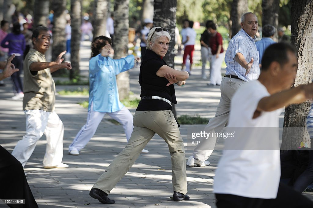 A foreign tourist (C) practices tai chi at a park in Beijing on September 17,2012. Chinese Premier Wen Jiabao hinted at new stimulus measures to boost flagging growth, while vigorously defending his decade in charge of the world's second-largest economy as Beijing approaches a sensitive leadership transition.