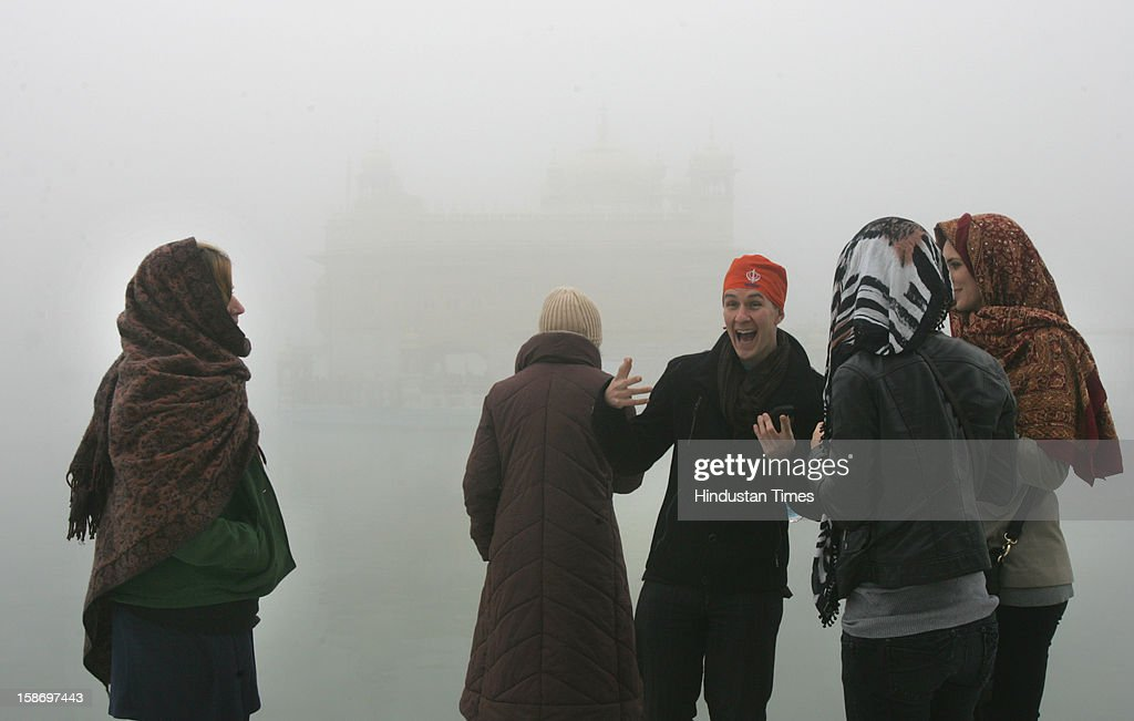 A foreign tourist reacts to cold weather while standing with his group as fog enveloped Sanctum of Harmandar Sahib (Golden Temple) Complex on December 24, 2012 in Amritsar, India. Heavy fog in the region causes several flights and trains delayed.