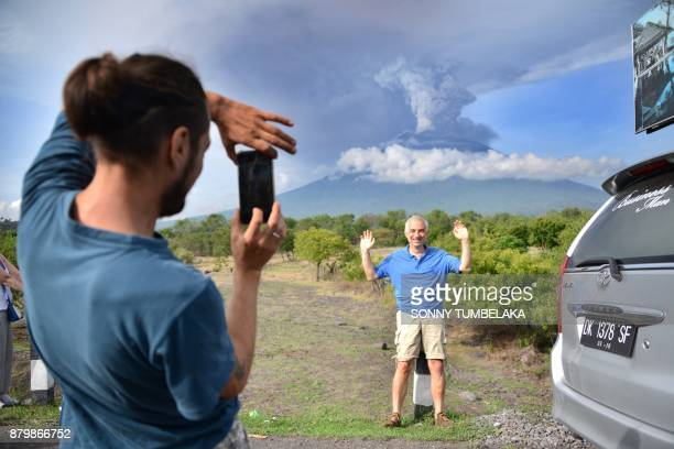 A foreign tourist takes pictures in front of Mount Agung erupting seen from Kubu subdistrict in Karangasem Regency on Indonesia's resort island of...