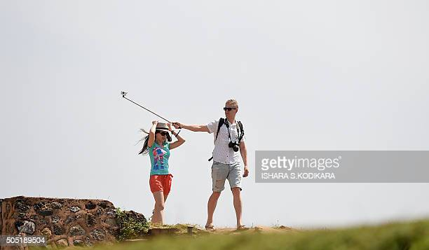 A foreign tourist uses a 'selfie' stick as he walks with his companion at the Galle fort in Galle on January 16 2016 The number of foreign tourists...