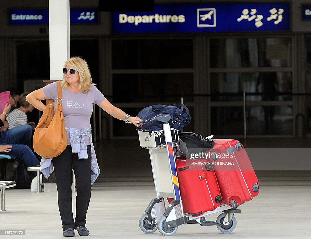 A foreign tourist waits with luggage at the Maldives International Airport in Male on November 12, 2013. The United States stepped up its criticism of the embattled Maldives on Tuesday, warning caretaker president Mohamed Waheed that a decision to remain in office after his mandate expired was endangering democracy. The US State Department said Waheed's move to continue to govern after his time in office lapsed at midnight Sunday was unprecedented, after the tourism-reliant Indian Ocean nation failed to hold elections for the third time in two months. AFP PHOTO/Ishara S. KODIKARA