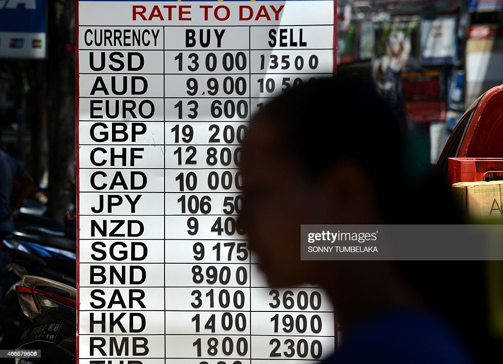 A foreign tourist walks past a money changer at Kuta on Bali island on March 17 2015 Indonesia will soon allow tourists from an additional 30...
