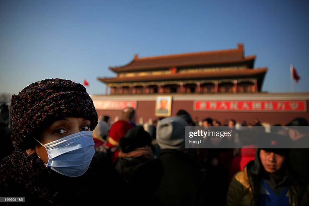 A foreign tourist wearing the mask at the Tiananmen Square during slight pollution on January 17, 2013 in Beijing, China.