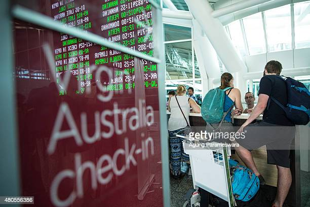 Foreign tourists ask their flight information at Ngurah Rai international airport departure on July 13 2015 in Denpasar Bali Indonesia Bali's...