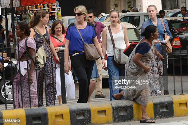 Foreign tourists cross a street in downtown New Delhi on October 8 2013 India is looking at issuing visas on arrival for visitors from 40 more...
