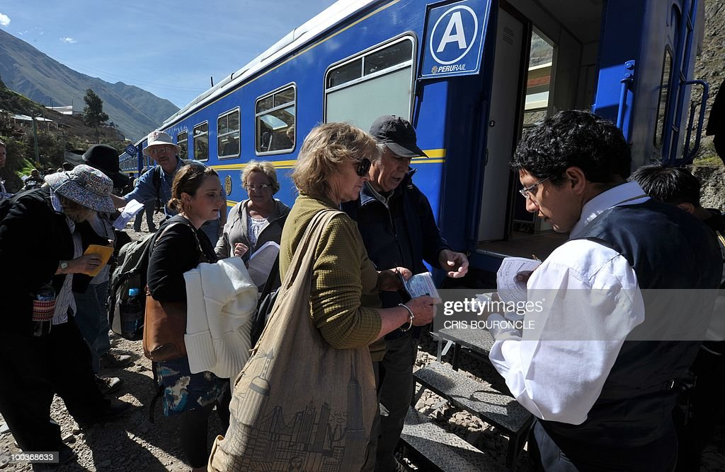 Foreign tourists embark on the train to the citadel of Machu Picchu at an intermediate station between the Andean city of Cuzco and the Inca fortress on May 23, 2010 as works to reconstruct the railroad line continues after it was destroyed by the Vilcanota River during the heavy rains that hit this area 1,200 kilometers southeast of Lima last January. The rains isolated hundreds of tourists and collapsed the tourism industry in the city of Cuzco and Machu Picchu during several weeks which regularly receives over 1,000 visitors a day.