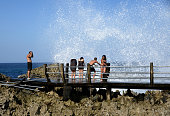 Foreign tourists enjoy water hitting the shore at a beach in the Nusa Dua resort island in Bali on August 27 2013 US President Barack Obama will join...