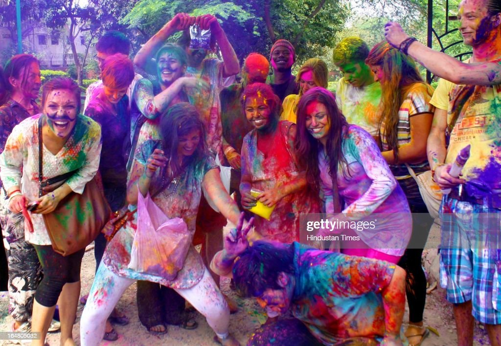 Foreign tourists enjoying Holi celebration near Malviya Nagar market on March 27, 2013 in New Delhi, India. Holi, festival of color is Hindu religious festival also called Basantotsav or spring festival as it mark the arrival of spring. People gather together to play colors, sing and dance to traditional tunes and eat sweets specially Gujiyas.