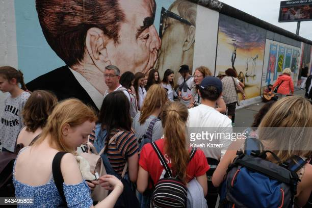 Foreign tourists gather around the mural depicting Leonid Brezhnev and Erich Honecker kissing painted by Dmitri Vrubel in The East Side Gallery on...