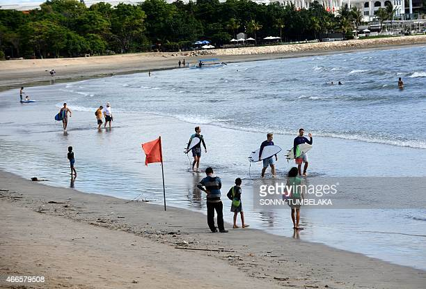 Foreign tourists hold surf boards as they wade into the waters off Kuta beach Bali island on March 17 2015 Indonesia will soon allow tourists from an...