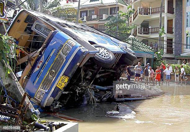 Foreign tourists look at damage caused by a tsunami in Phuket island southern of Thailand 26 December 2004 At least 118 people were killed and 1300...